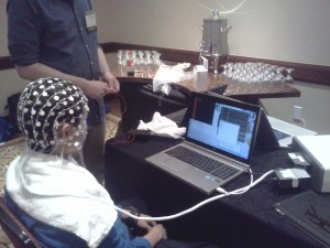 A volunteer is wired up to a Brain-Computer Interface consisting of a skull cap with dozens of electrodes